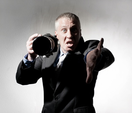 Emotional photographer in a suit with a camera photo