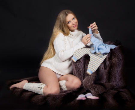 Beauty pregnant woman with baby clothes photo
