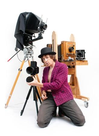 weirdo: Creative photographer in pink coat with retro camera