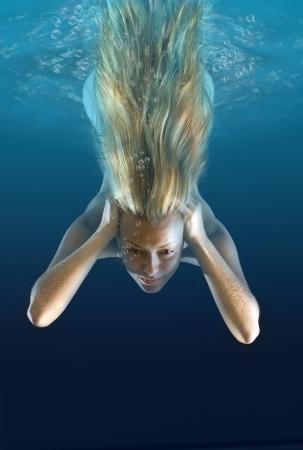 Beautiful naked girl swims under water photo