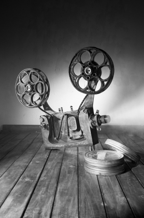 Movie projector with the film on the wooden floor photo