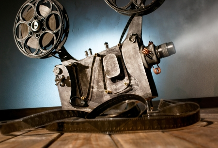 vintage camera: Movie projector with the film on the wooden floor