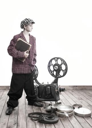 Tiener met een boek en een cinema projector Stockfoto