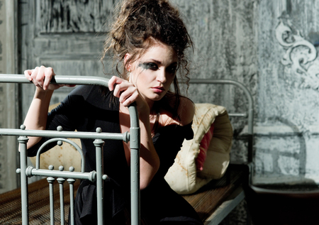 Young sad woman sitting on the old bed Stock Photo