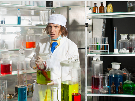Scientist chemist puts science experiment in laboratory photo