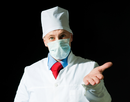 Portrait of doctor in surgical mask on black  photo