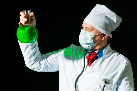 Doctor in surgical mask holding the flask photo