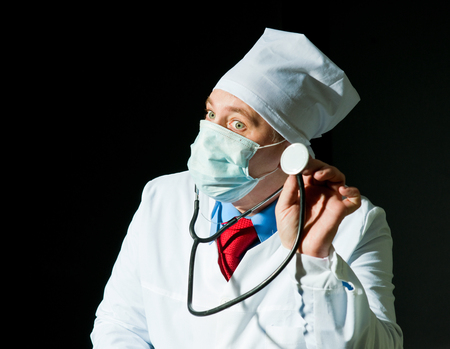 Doctor in surgical mask holding stethoscope photo