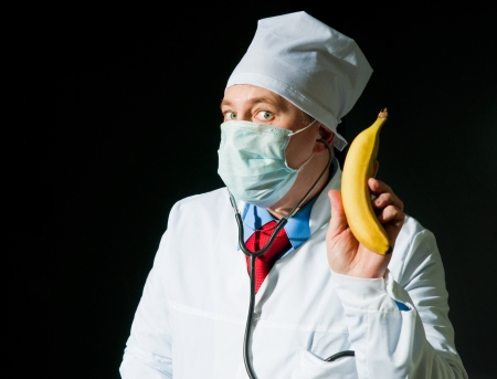 Doctor in surgical mask with the ripe banana photo
