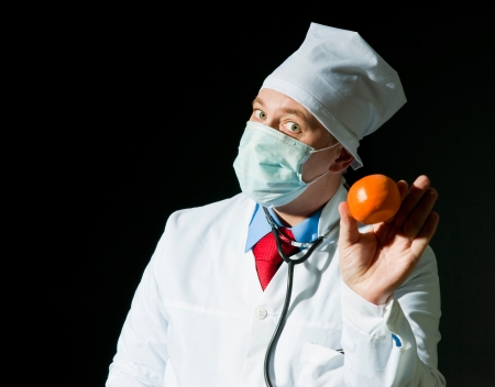 Doctor in surgical mask with the ripe tangerine photo
