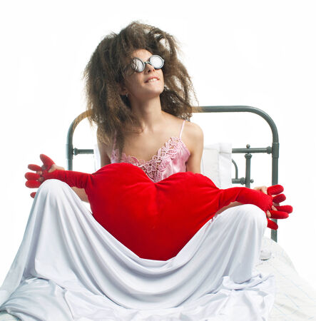 Girl with red heart sitting on the bed photo