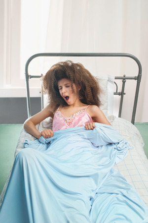Girl wakes up in bed in the morning