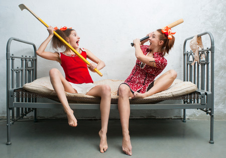 flogging: Two women fight on the bed Stock Photo