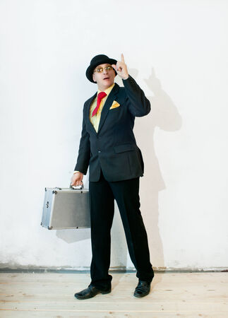 Businessman in black suit with a suitcase photo