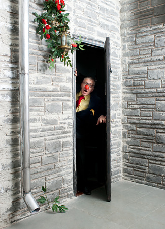 furtively: Cautious man peeping from behind the door