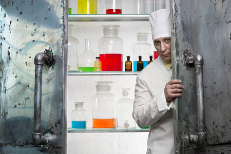 profess: Chemist looks from behind the door of the laboratory
