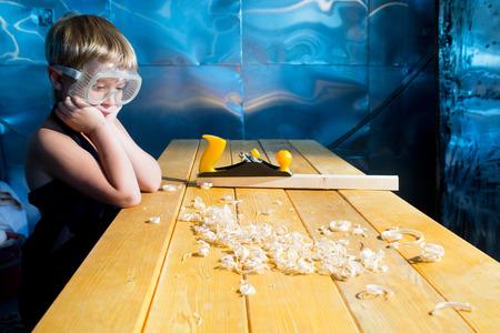plane table: Peque�o carpintero con el plano de afeitado en la mesa Foto de archivo