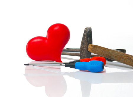 faithlessness: Red heart and tooling on the white background Stock Photo