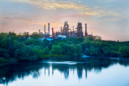 steel works: Metallurgical works on the background of trees and river