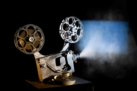 old movies: Movie projector with the film on the black background