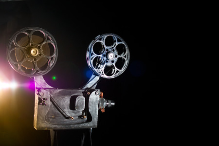 metier: Movie projector with the film on the black background