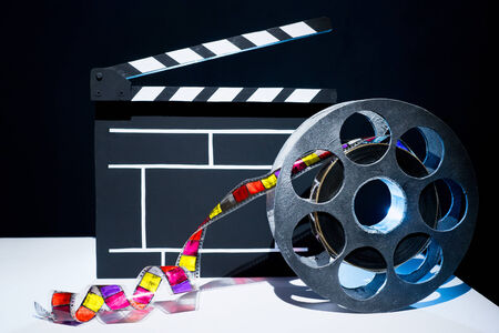 performing: Cinema clapper and reel of film on the black background Stock Photo