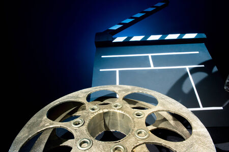 Cinema clapper and reels of film on the black background photo