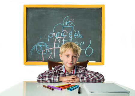 assiduous: Schoolboy sits at his desk by the blackboard