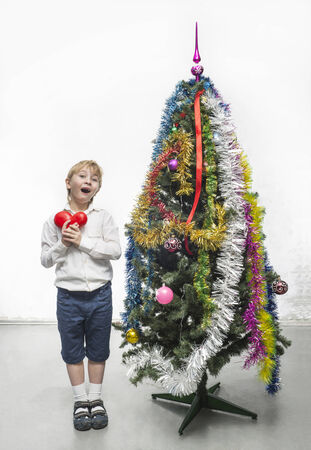 Little boy decorates a Christmas tree photo