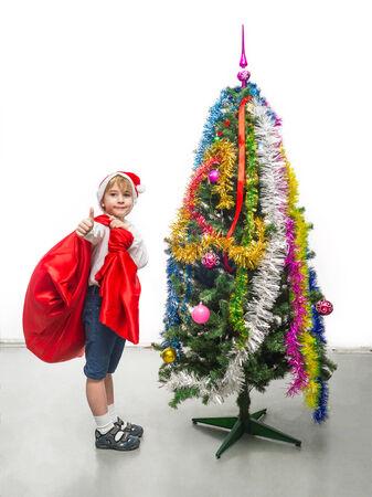 Little Santa with a sack near the Christmas tree photo