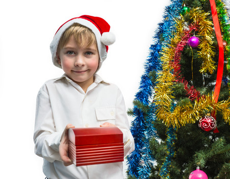 Little Santa with a gift near the Christmas tree photo