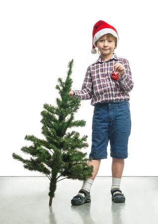 Little Santa decorates a Christmas tree photo