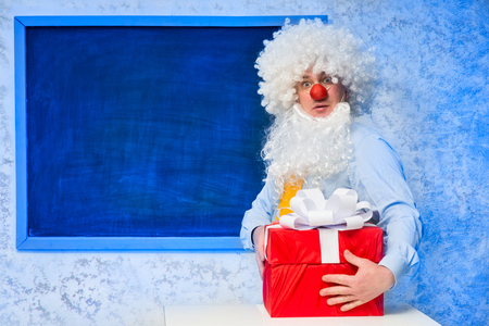 Santa Claus with gifts near the blackboard photo