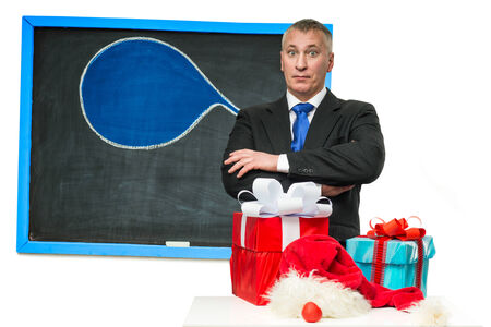 Businessman with Christmas gifts near the blackboard photo