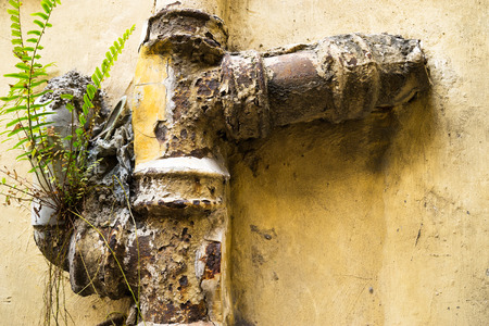 parget: Old water pipe in wall of house