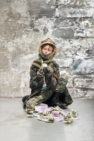 venality: Teenager in uniform of soldier with money