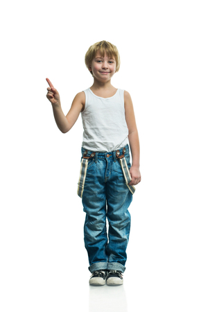 Smiling boy in jeans on the white background photo