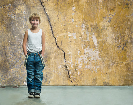 Boy in jeans stands near a wall photo