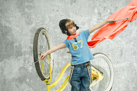red scarf: Boy in a red scarf repairing a bicycle Stock Photo