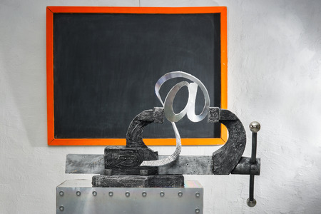 grip: Sign of e-mail in grip on a background of blackboard Stock Photo