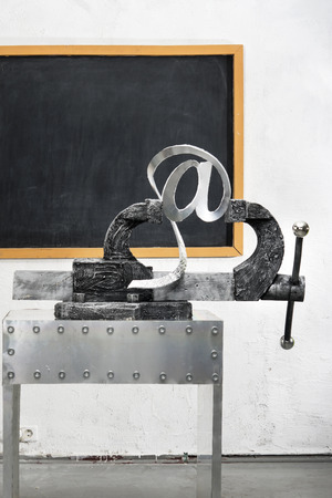 vise grip: Sign of e-mail in grip on a background of blackboard Stock Photo