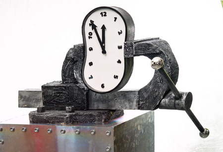 A time in a vise on a background of white wall