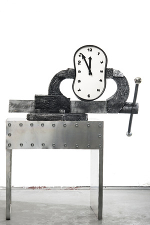 constricted: A time in a vise on a background of white wall