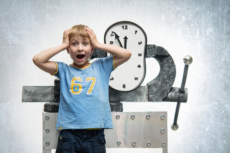 vise: A frightened boy and clock clamped in a vise
