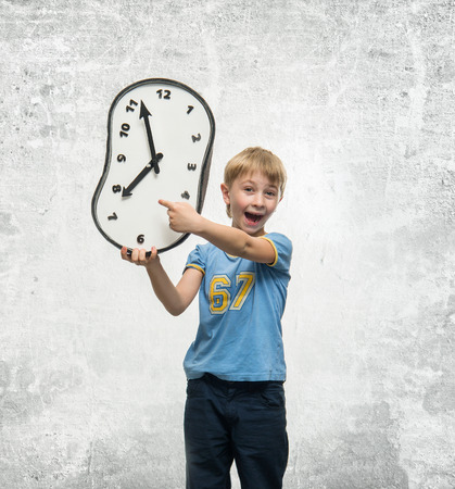 exactness: Boy holding a clock in his hands