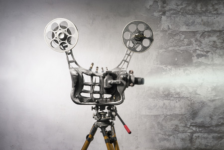industry background: Movie projector with the film on the background of wall