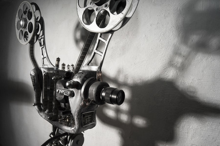 Movie projector with the film on the background  of gray wall