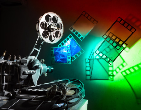 film: Cinema projector and a film pieces on the bright background