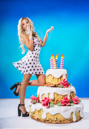 nude art model: Sexy young woman eating a big birthday cake Stock Photo