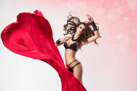 nude art model: Pretty woman in a black lingerie with a silk red fabric Stock Photo